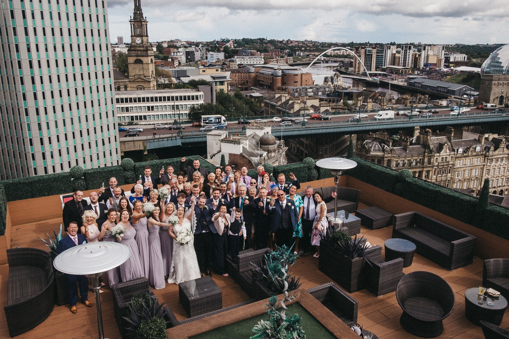 A group shot from Emma & Ian's wedding in the Sky Lounge on top of the Vermont Hotel, looking out over Newcastle and Gateshead