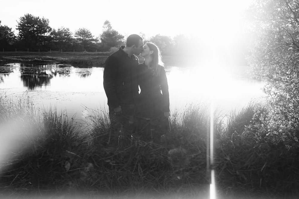 A black and white photo of a couple kissing in front of a lake, reflected in a prism