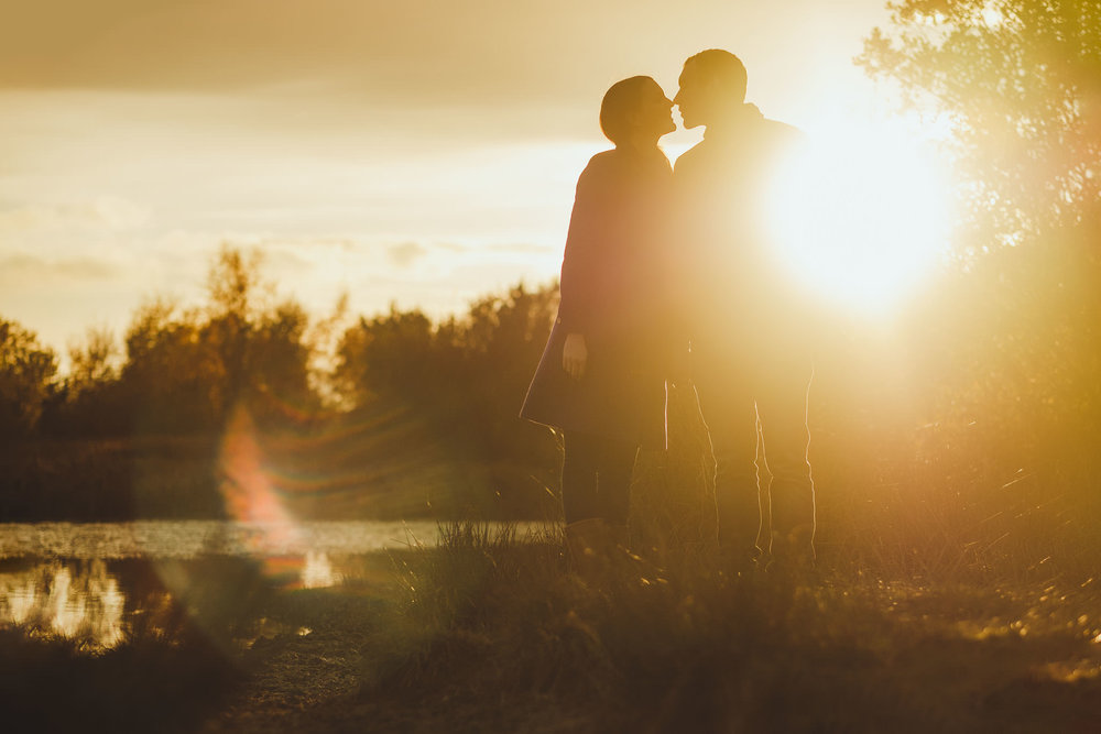 Sunset photo of couple kissing in a nature reserve in Newcastle