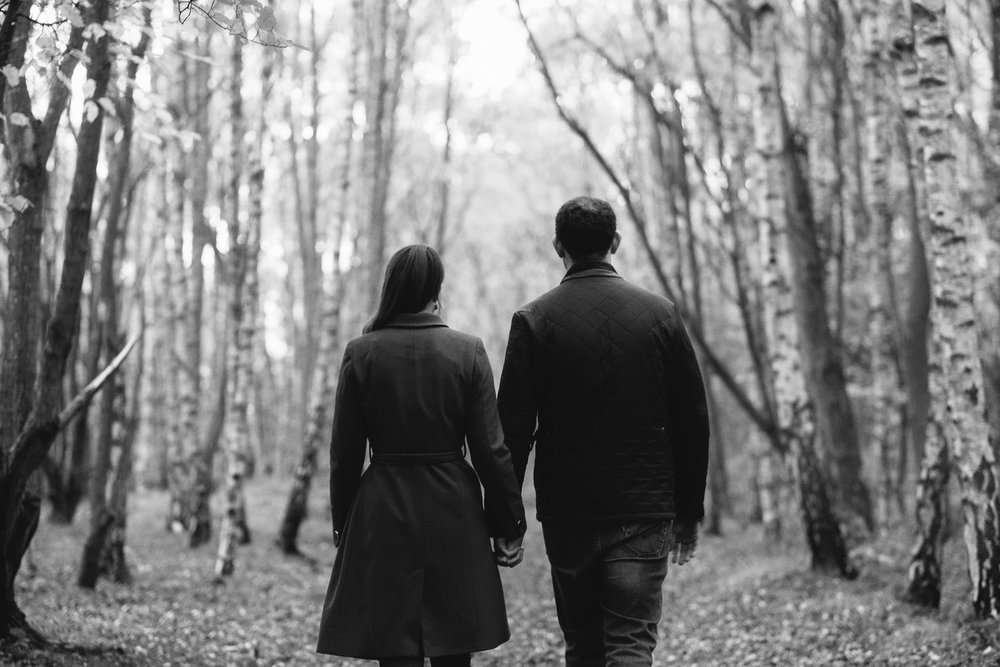 A black and white photograph of a couple holding hands and walking into a forest in Newcastle