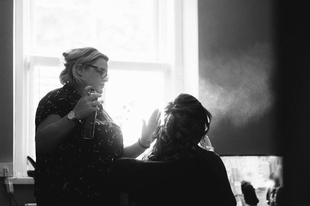 A black and white photo of bridesmaid's hair styling