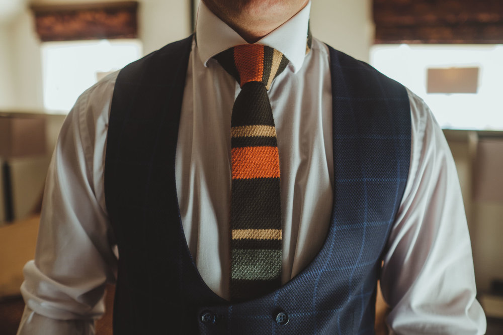 Close up of groom's colourful tie