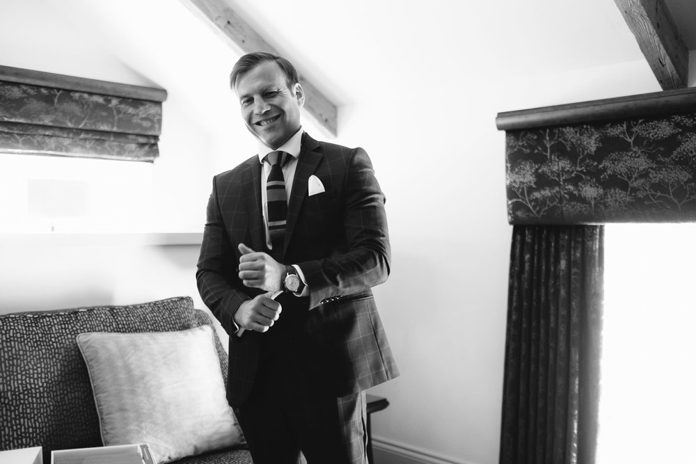 A black and white photo of the groom putting on the watch that was a gift from his bride