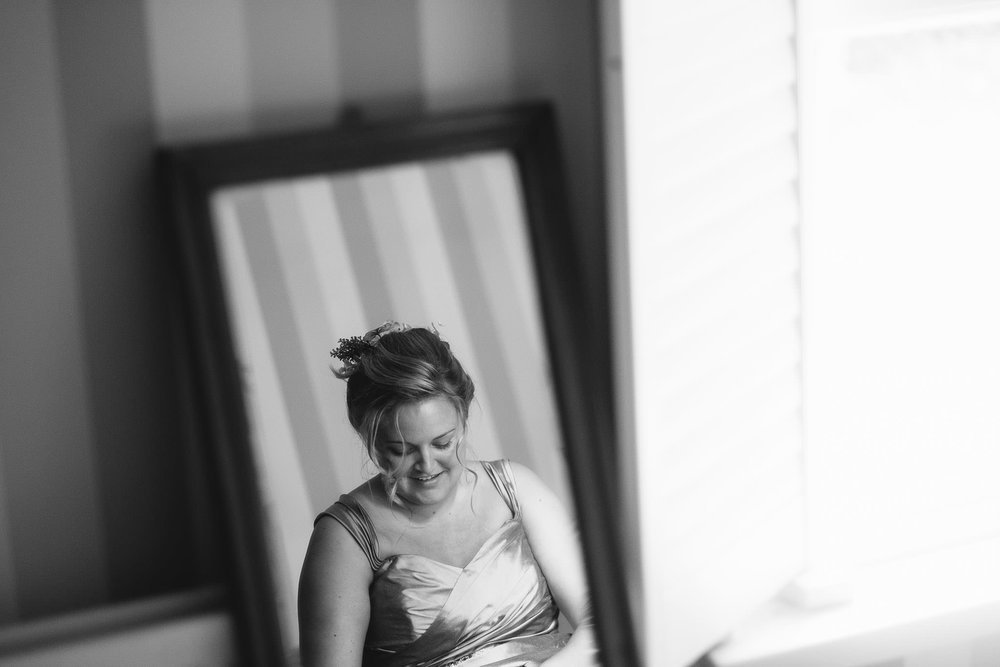 A black and white photo reflection in a mirror of the bride getting ready