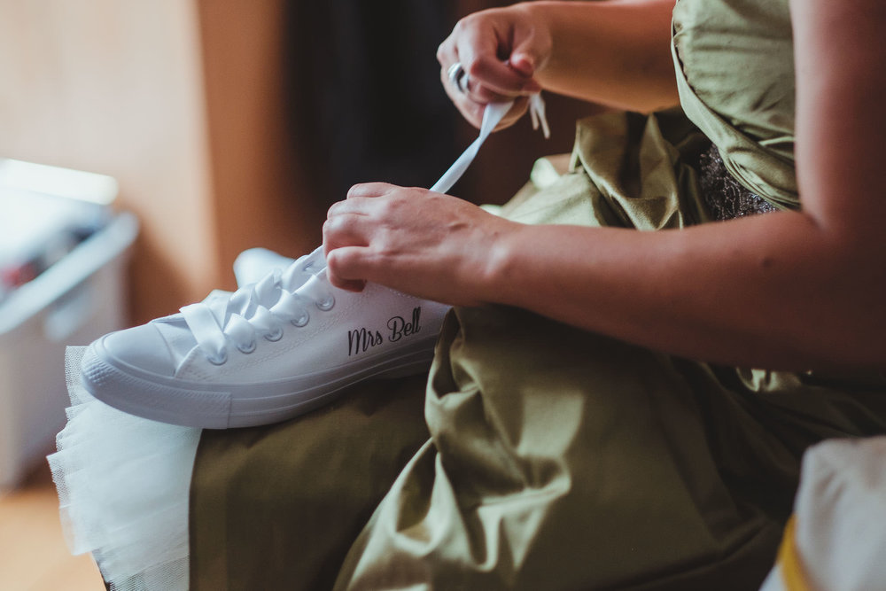 Bride lacing her personalised Converse before the wedding