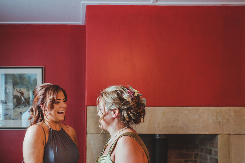 Bride and bridesmaid laugh before the wedding ceremony