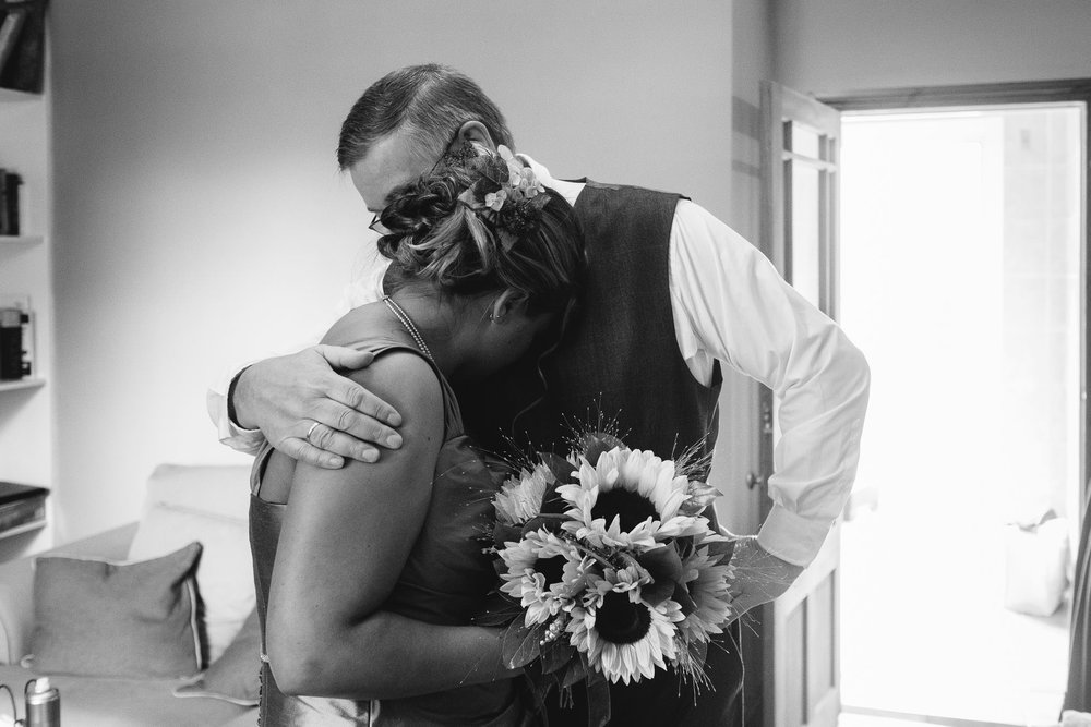 A black and white photo of the emotional bride and her father hugging before the ceremony