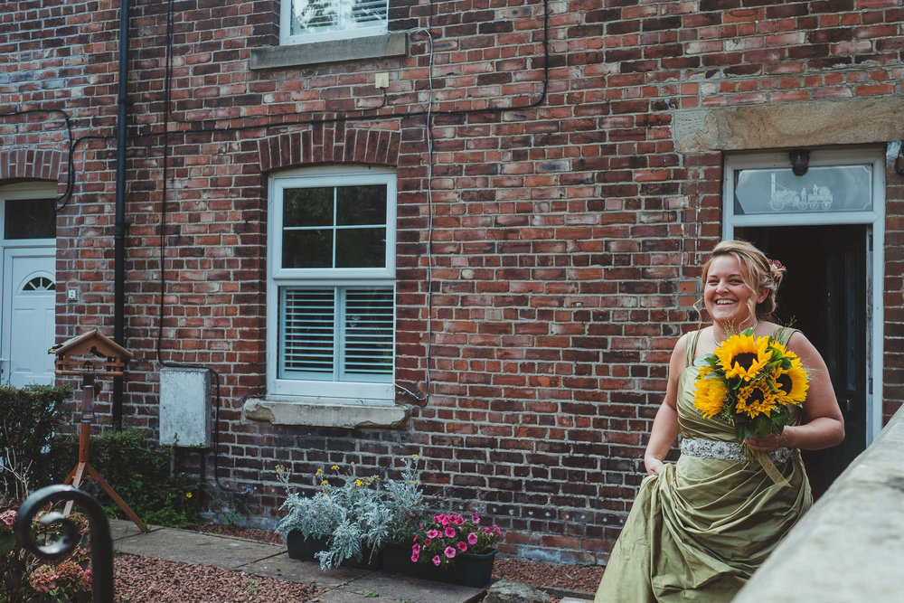 Bride smiling as she leaves her house in Newcastle for the wedding