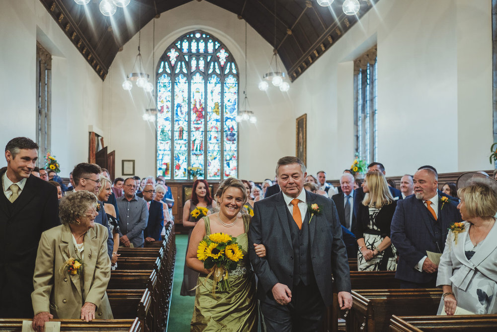 Bride is walked down the aisle of the church by her dad