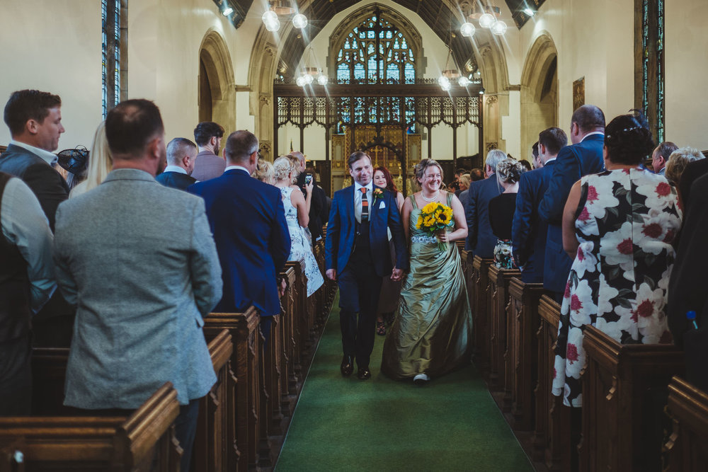 Bride and groom leave the church after their wedding ceremony