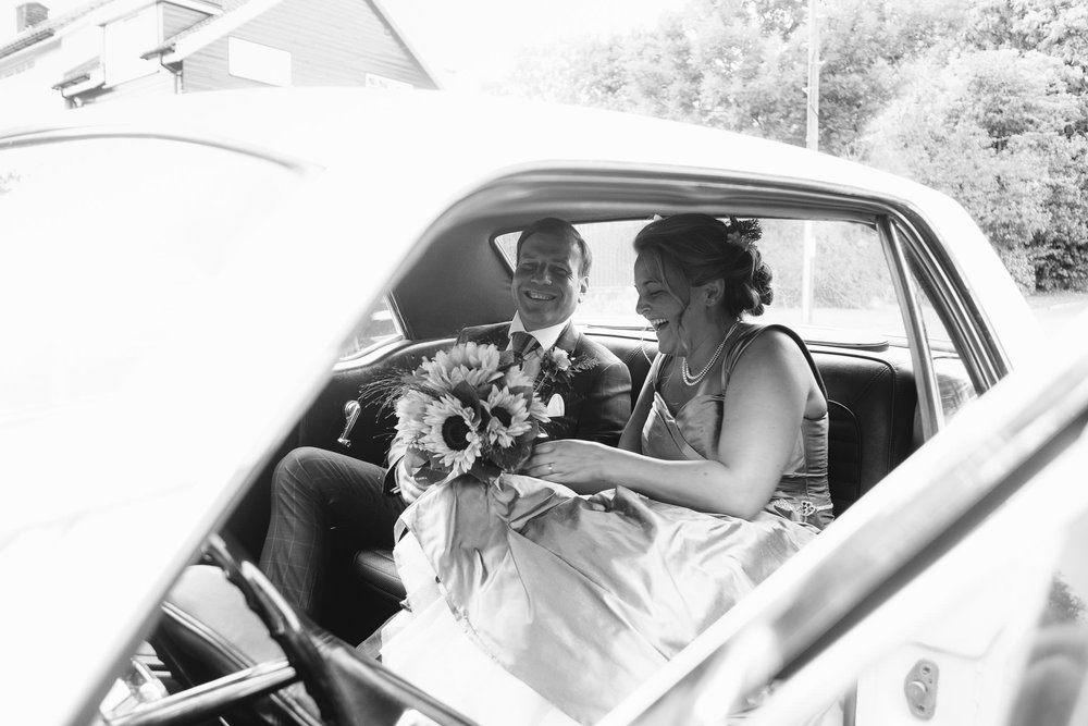 A black and white photo of the bride and groom getting in the car after their wedding ceremony