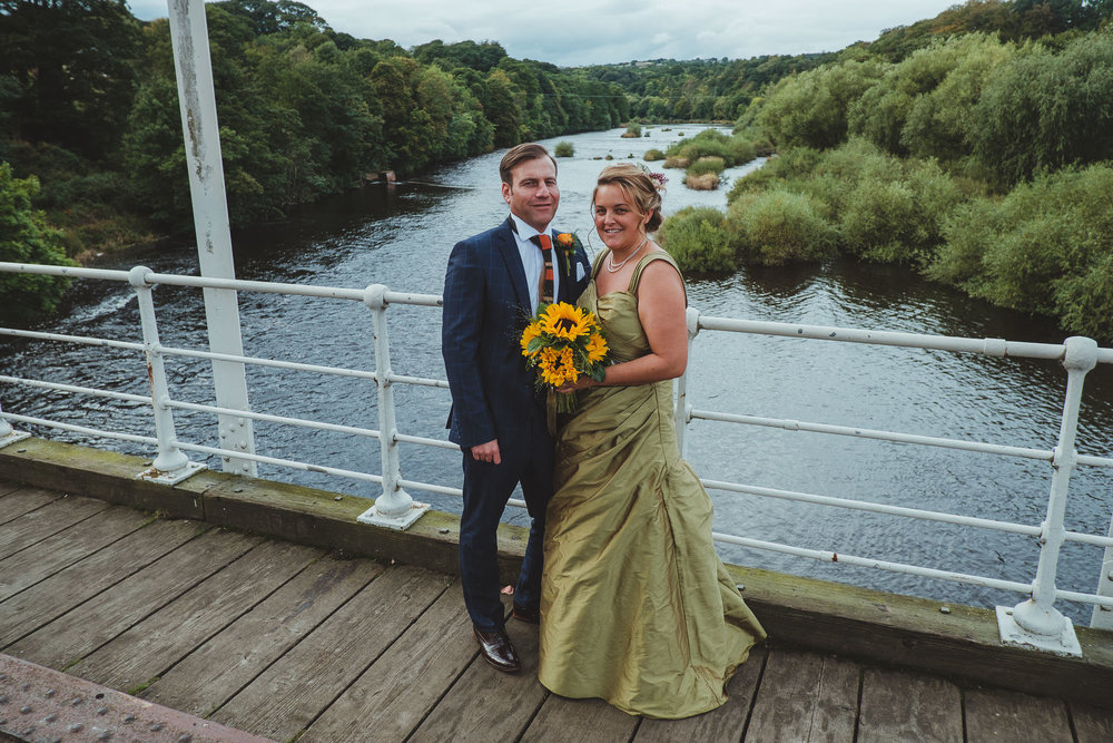Bride and groom pose on a bridge over the River Tyne