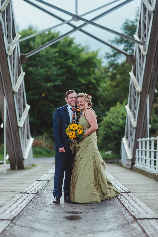 Bride and groom hug on the bridge at Hagg Bank