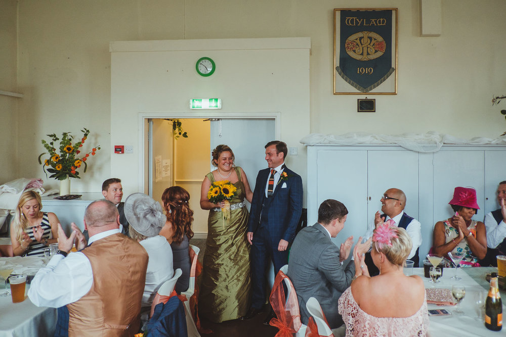 Bride and groom laugh as they enter wedding reception