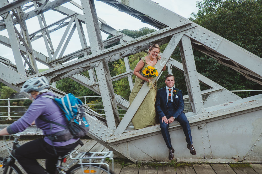 Bride and groom sit on bridge while cyclists ride past