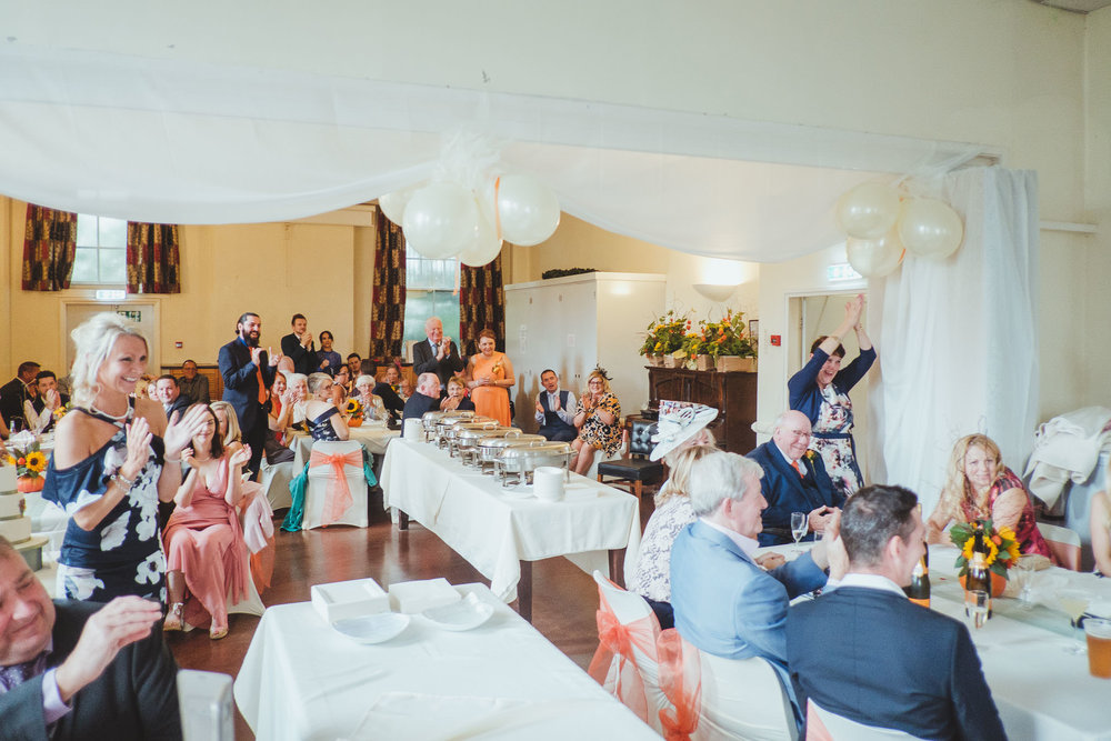 Wedding guests cheer and clap as bride and groom arrive