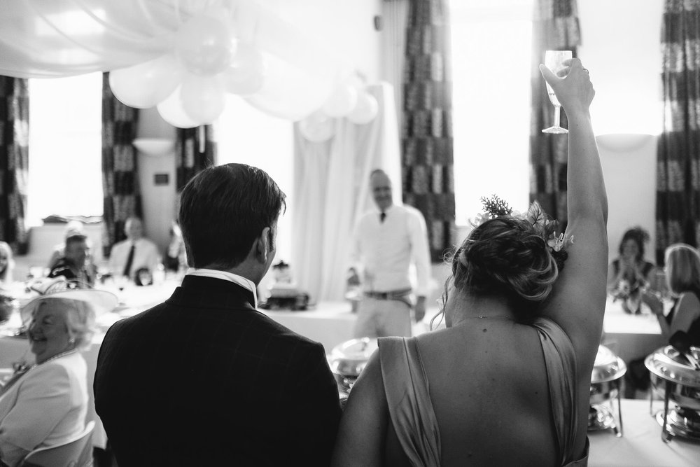 A black and white photo of the bride and groom toasting a wedding speech