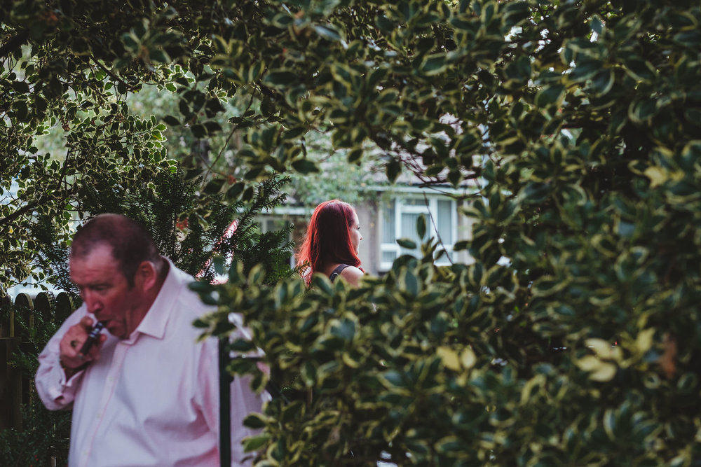Wedding guests smoking near bushes outside Wylam Institute