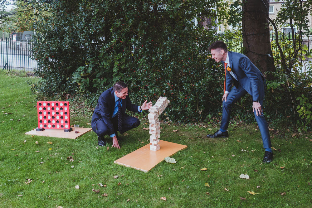 Giant Jenga pieces falling as wedding guests play