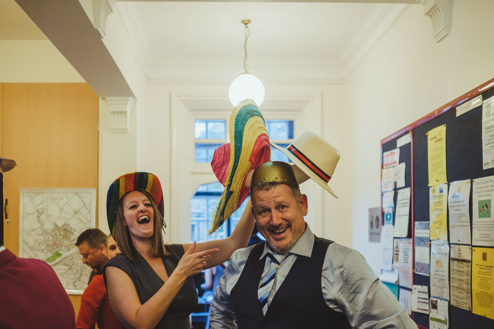 Wedding guests putting on multiple hats for photo booth fun