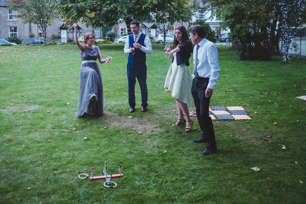 Bridesmaid punches the air as she wins a game of quoits