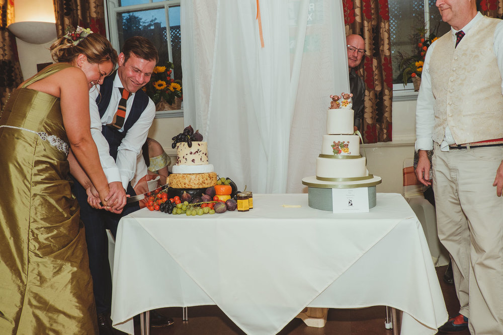 Bride and groom cut the cheese wheel
