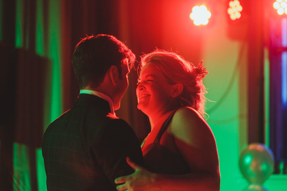 Close up of bride and groom first dance in green and red light