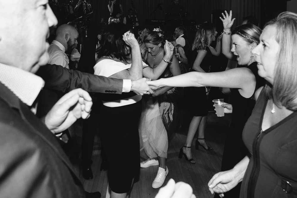 A black and white photo of the wedding guests on the dance floor