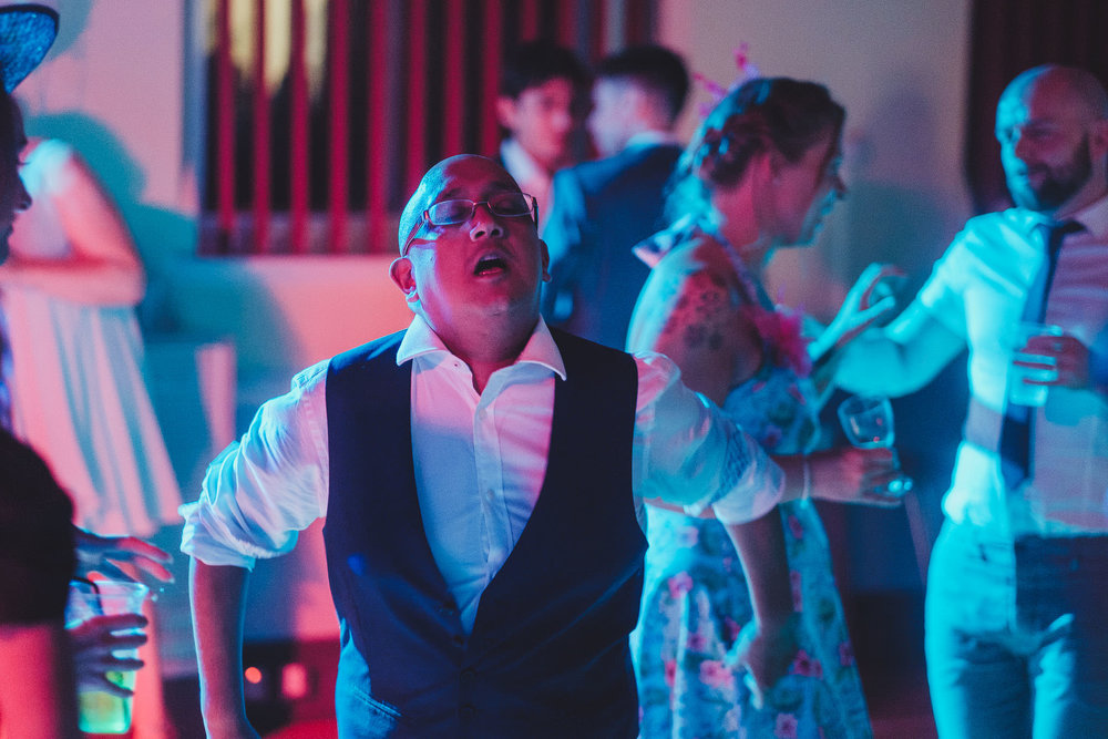 A wedding guest dancing and singing bathed in colourful light