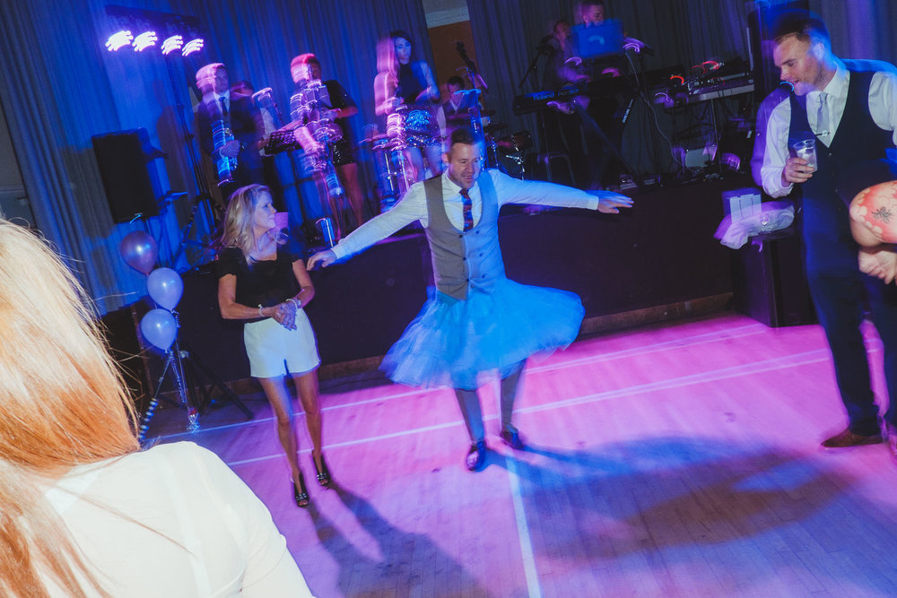 A male wedding guest dances in a blue tutu