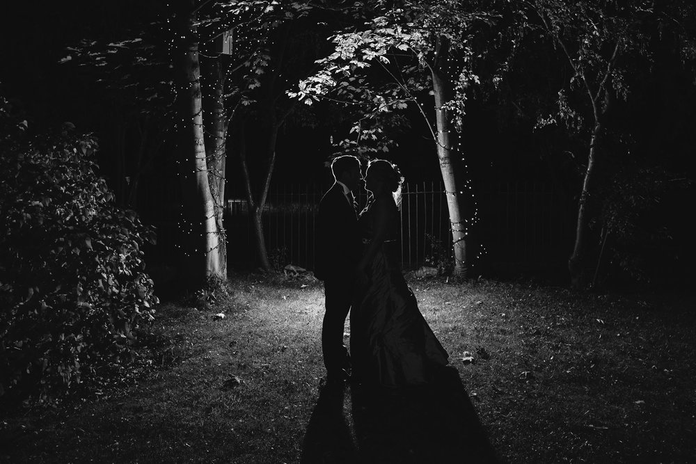 A romantic black and white photo of the bride and groom embracing at night, lit from behind