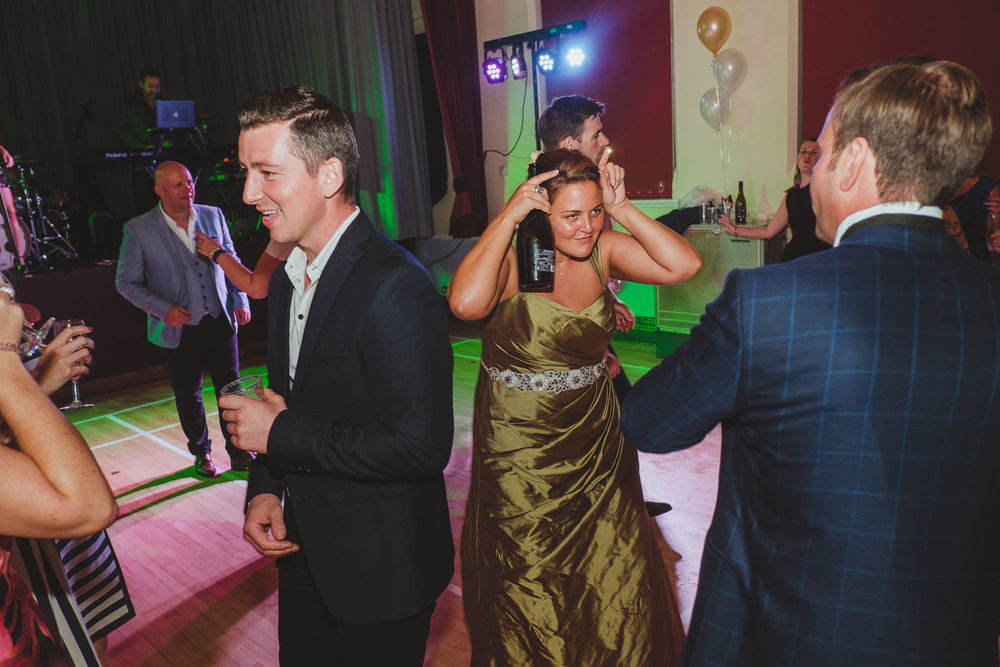 The bride makes devil horns on the dance floor