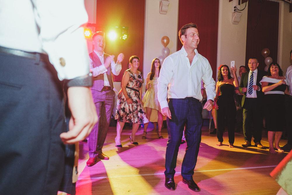 The groom dancing after his tie has been stolen