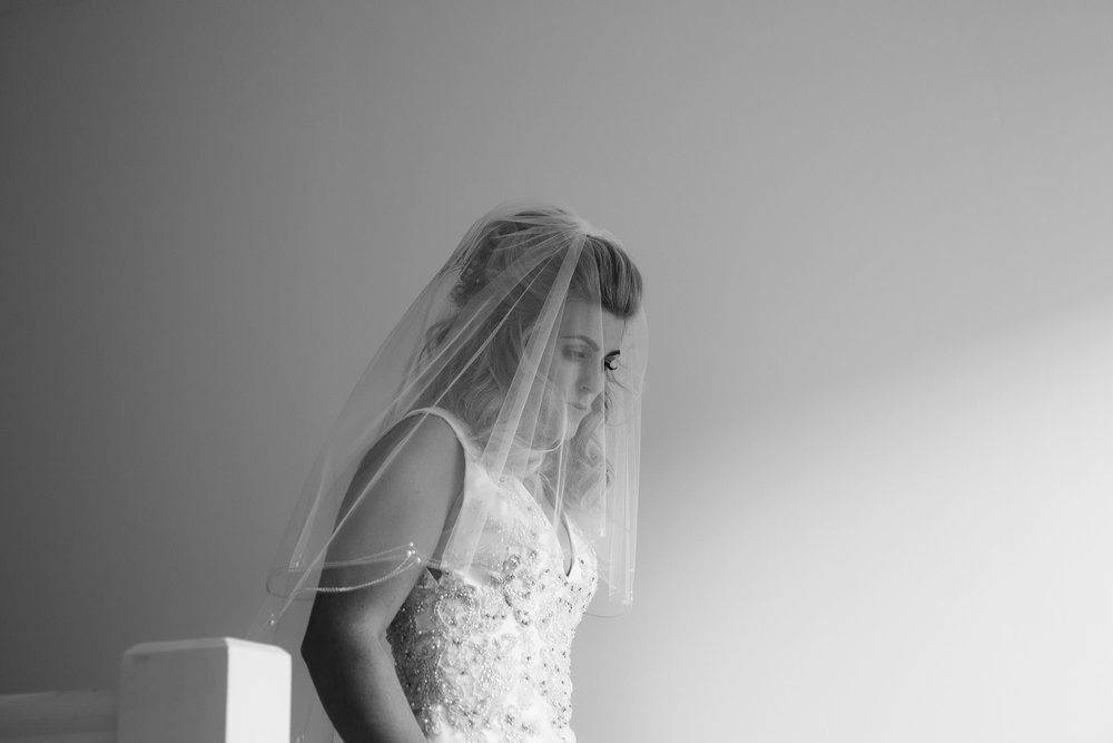 A black and white photo of the bride in her veil before the ceremony