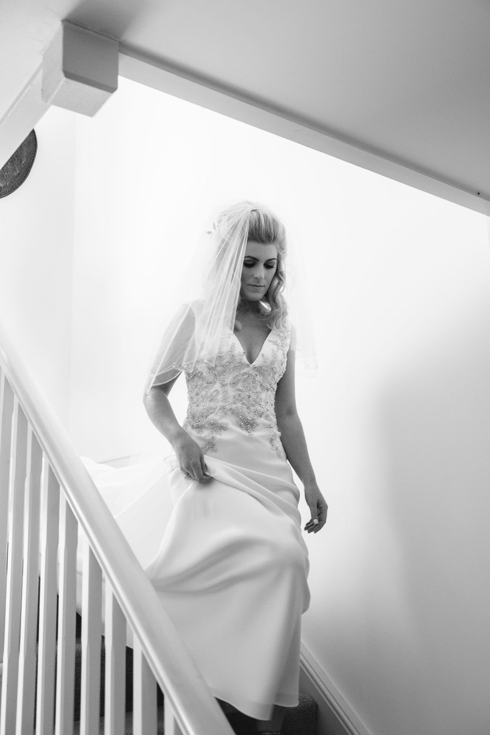 A black and white photo of the bride walking down the stairs