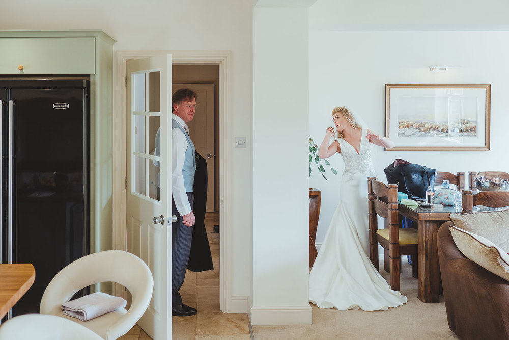 The bride checks herself in the mirror while a groomsman gets ready