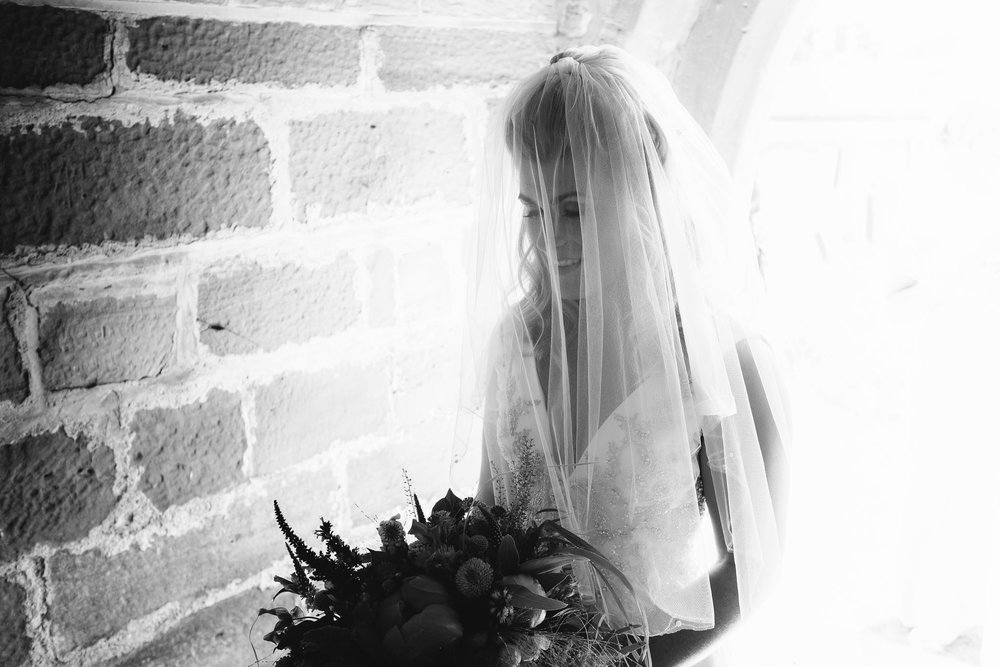 A black and white photo of the bride waiting to enter the church
