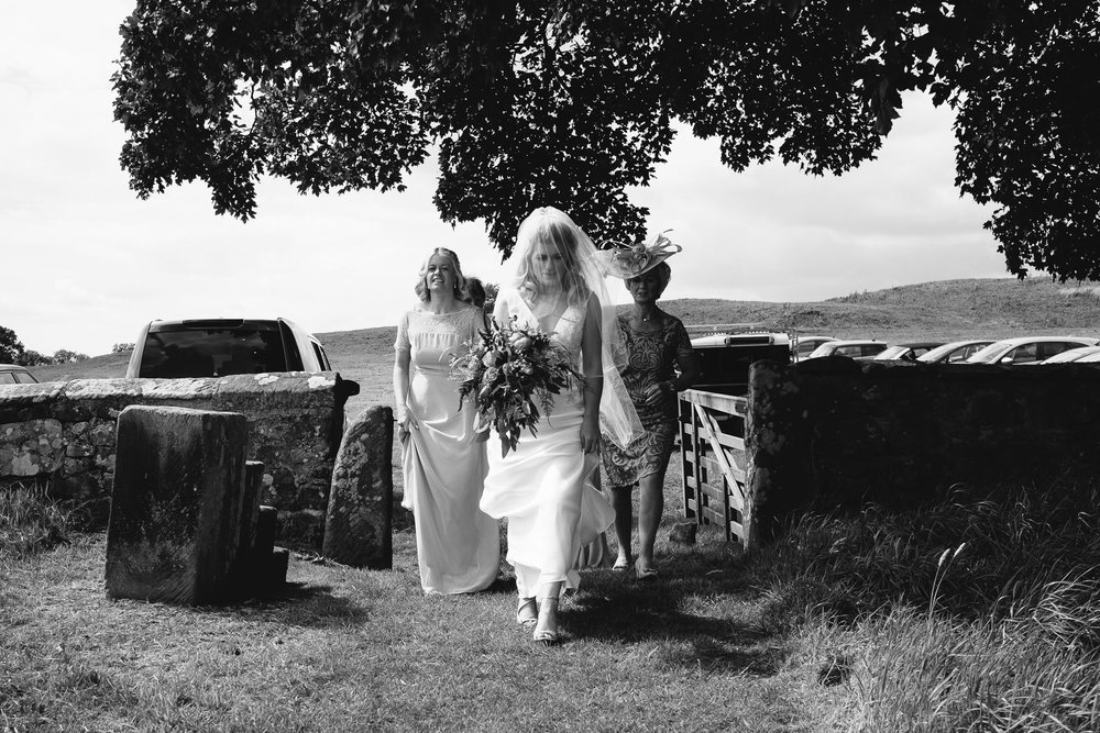 A black and white photo of the bride and her bridesmaids walking to the church