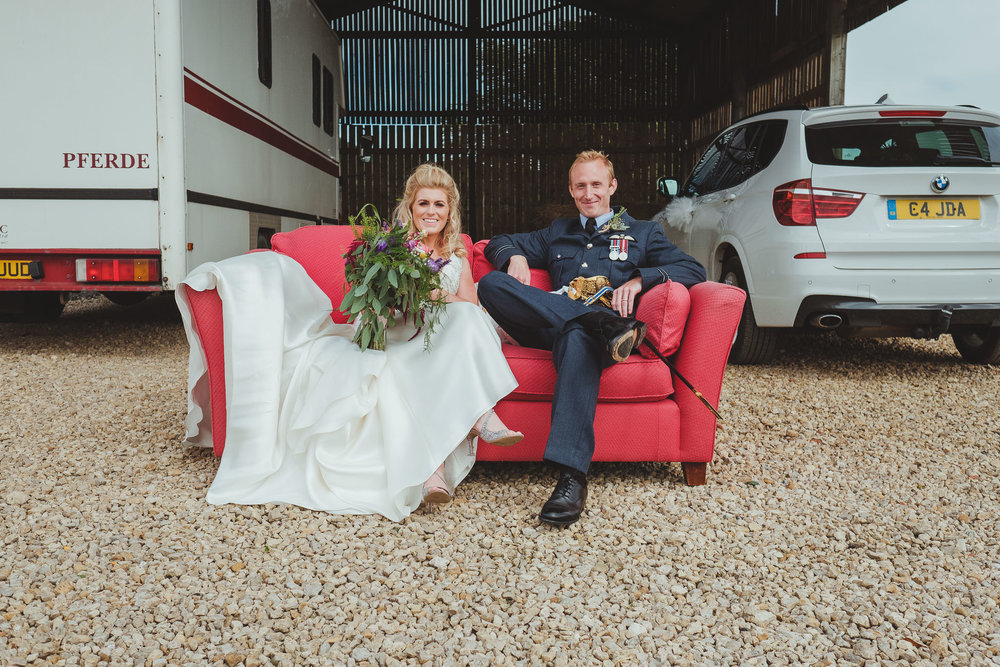The bride and groom sit outside on a red sofa