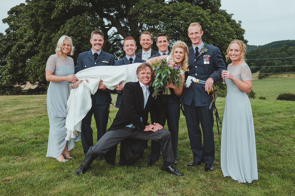 The bride is held up by the groomsmen during her wedding group shots