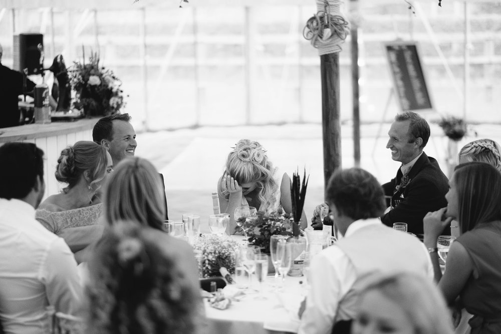 A black and white photo of the bride being embarrassed during a wedding speech