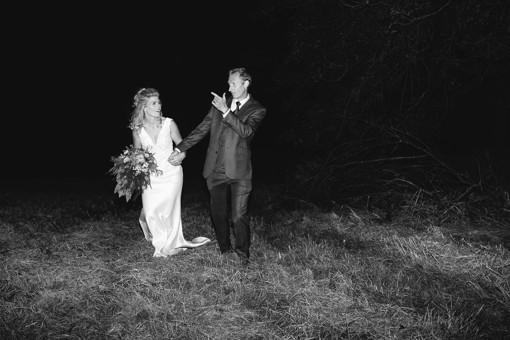 A black and white photo of the bride and groom pulling silly poses at night