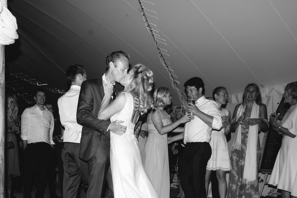A romantic black and white photo of the bride and groom kissing during their first dance
