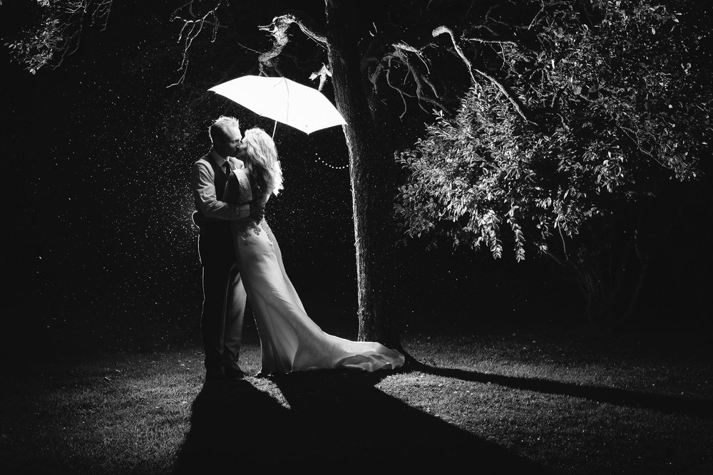 A romantic black and white photo of the bride and groom kissing under an umbrella in the rain