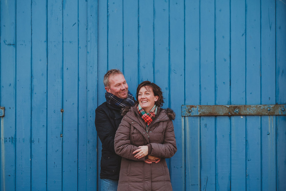 Couple cuddling and laughing in front of blue door on pre wedding session in Newcastle