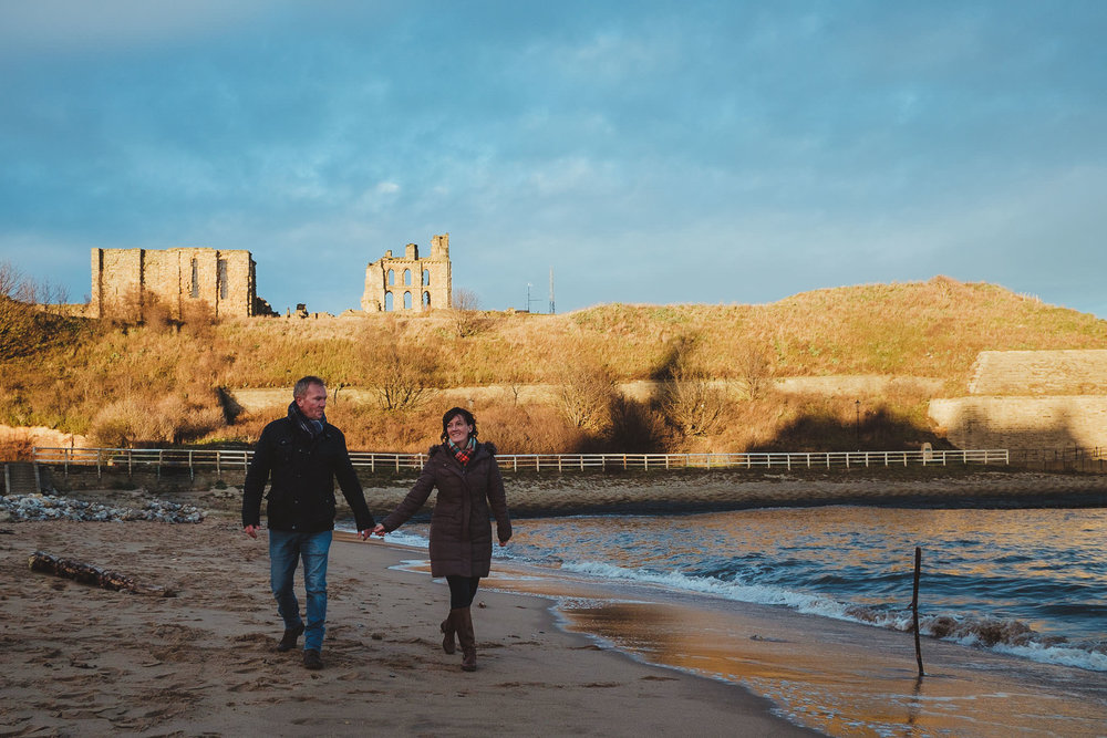 Couple walk hand in hand along beach at Tyneside Newcastle