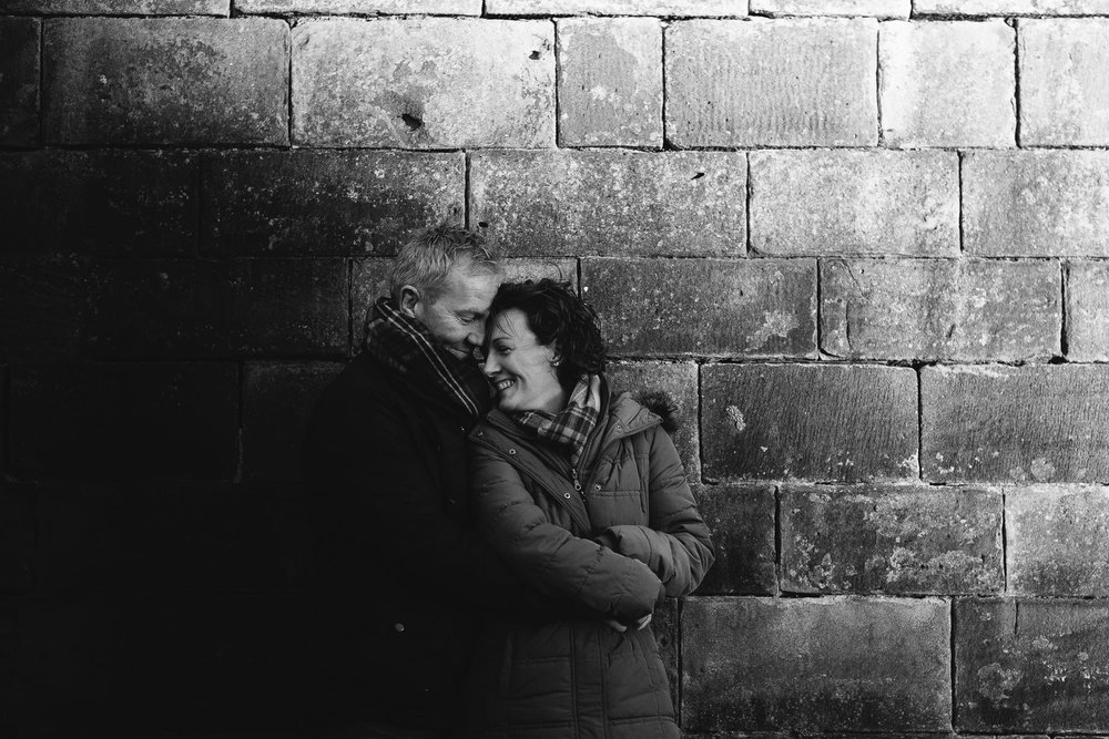 Black and white photo of couple cuddling in front of sandstone wall in Newcastle