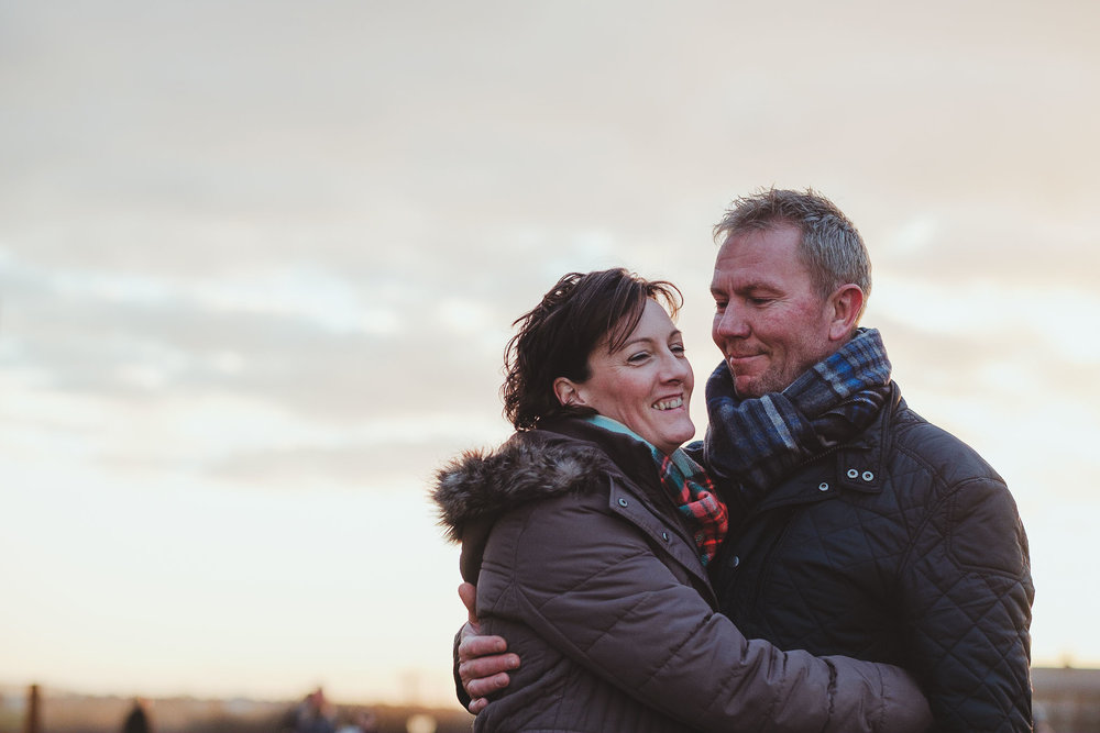 Couple cuddle and smile while on pre wedding session on Tyneside coast