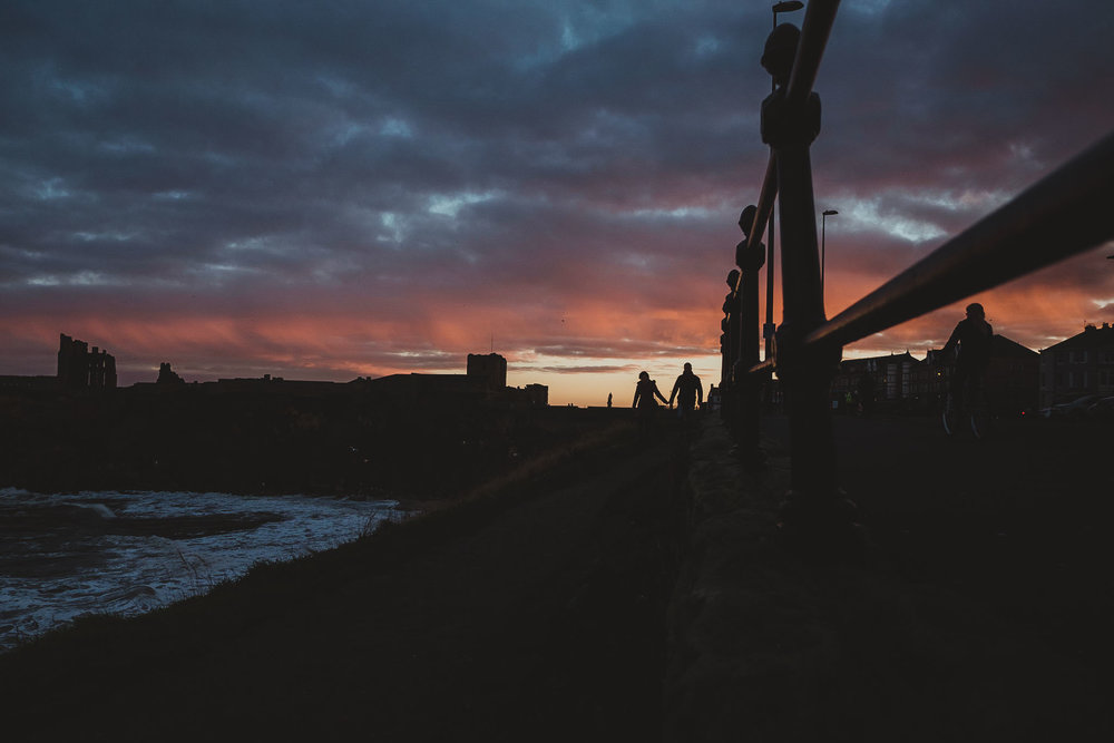 dramatic sunset photo of couple holding hands with Tynemouth Priory in background