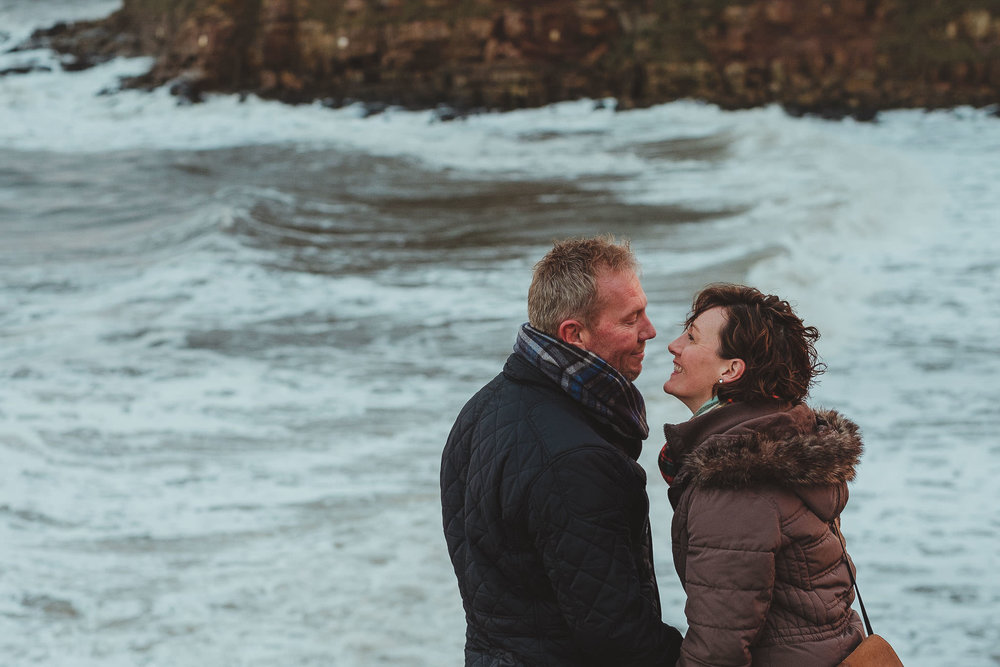 Couple lean in for a kiss on pre wedding session with sea waves behind them
